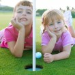 Golf sister girls relaxed laying green hole ball - Стоковая фотография