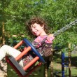 Girl swinging on swing happy in trees outdoor — Stock Photo