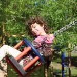 Girl swinging on swing happy in trees outdoor — Stock Photo