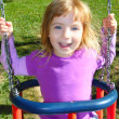 Girl swinging on swing happy in meadow grass park — Stock Photo #5514165