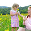 Daughter and mother playing in flowers meadow — Stock Photo