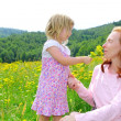Daughter and mother playing in flowers meadow — Stock fotografie