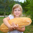 Girl holding big bread humor size hungry child — Stock Photo