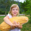 Girl holding big bread humor size hungry child — Stock fotografie