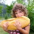 Girl eating big bread humor size hungry child — Stock Photo