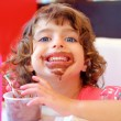 Girl eating chocolate ice cream dirty face — Stock Photo #5514243