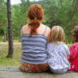 Mother and daughters sitting back park forest — 图库照片
