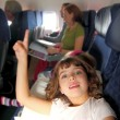 Little girl inside aircraft rising up finger — Stok fotoğraf