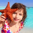 Royalty-Free Stock Photo: Little tourist girl holding starfish tropical beach