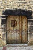Mittelalterliche holztür in stein wand pyrenäen — Stockfoto