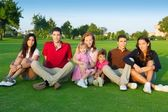 Family friends group sitting green grass — Stockfoto