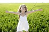 Open arms little happy girl green meadow field — Stock Photo