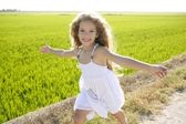 Running open arms little happy girl in meadow track — Stock Photo