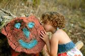 Girl kiss a cutted trunk with happy face draw — Stock Photo