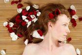 Redhead mooie vrouw, nam bloemblaadjes op haar — Stockfoto
