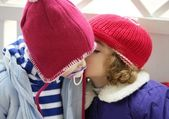Children, winter red hat whispering in ear — Stockfoto