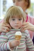 Beautiful toddler eating ice cream, mother care — Stock Photo