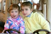 Two little sister girls driving car on fairground — Stock Photo