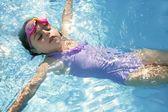 Beautiful girl swimming on blue pool — Stock Photo