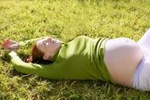 Pregnant woman redhead laying on grass — Fotografia Stock