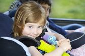Smiling little girl safety belt car security chair — Stock Photo