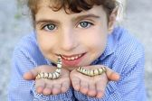 Little girl palying with silkworm in hands — Stock Photo