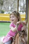 Little blond girl playing horses merry go round — Stock Photo