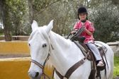 Rider little girl jockey hat white horse in park — Stock Photo