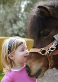 Little blond girl loves her donkey funny portrait — Stock Photo