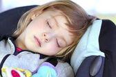 Little girl sleeping on children car safety seat — Stock Photo
