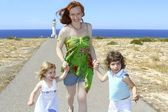 Mother two daughter sister running happy — Stock Photo