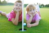 Golf sister girls relaxed laying green hole ball — Stock Photo