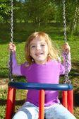 Girl swinging on swing happy in meadow grass park — Stock Photo