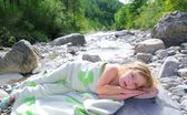 Girl towel in river lying relaxed after swimming — Stock Photo