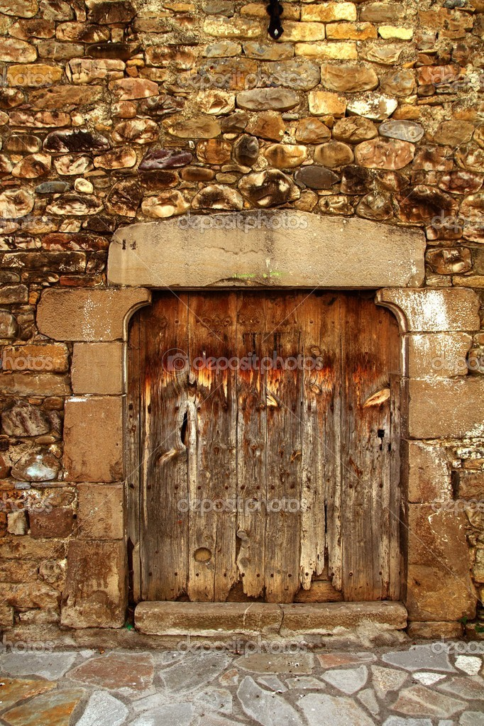 Aged wood door in medieval masonry Pyrenees house facade — Stock Photo #5510941