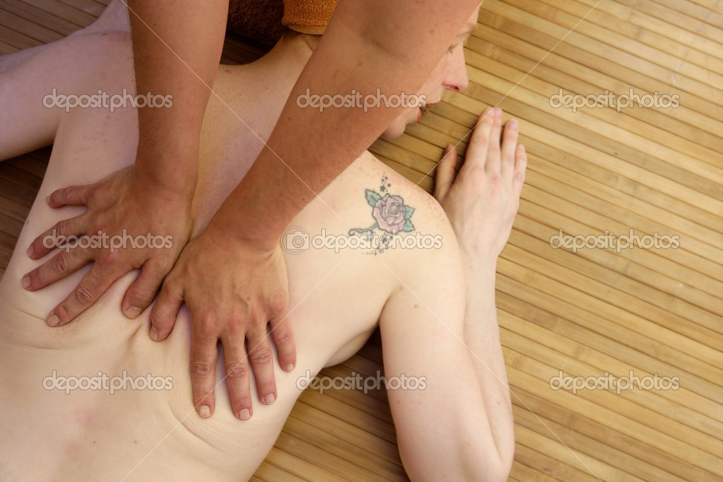 Beautiful woman receiving a back massage over bamboo spa — Stock Photo #5512887