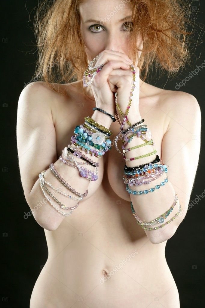 Sexy redhead woman with jewelry around her arms, over black
