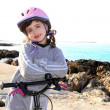 Bicycle little happy girl pink helmet in rocky sea — Stock Photo #5553907