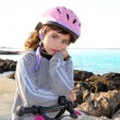 Bicycle little pensive girl pink helmet in rocky beach — Stock Photo #5553936