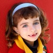 Smiling little girl indented front teeth smile on red — Stock Photo