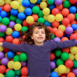 Colorful balls funny park little girl lying gesturing - Foto Stock
