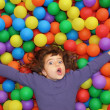 Colorful balls funny park little girl lying gesturing — Stock Photo #5554101
