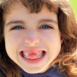 Indented girl sticking tongue between teeth - Stockfoto