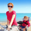 Daughter and mother on bicycle in beach sea — Stock Photo #5554237