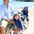 Daughter and father on bicycle in beach sea — Stock Photo
