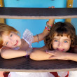 Blue eyes little sister girls similing in playground stairs — Stockfoto