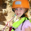 Climbing little girl smiling portrait helmet rope - Stock Photo