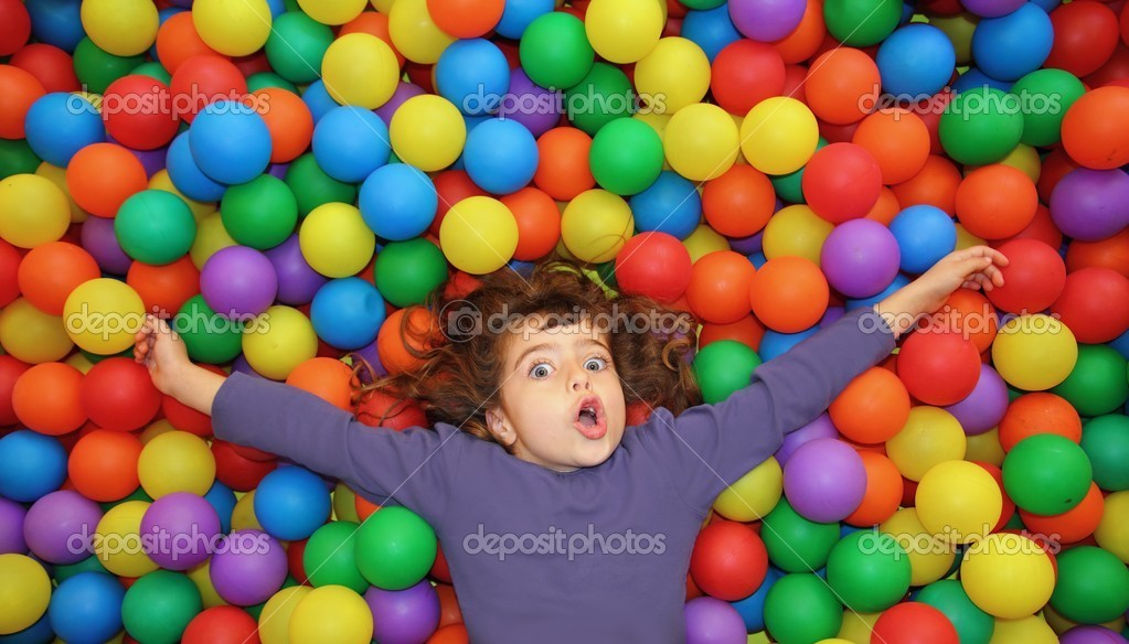 Colorful balls funny park little girl lying gesturing happy  Stock Photo #5554101
