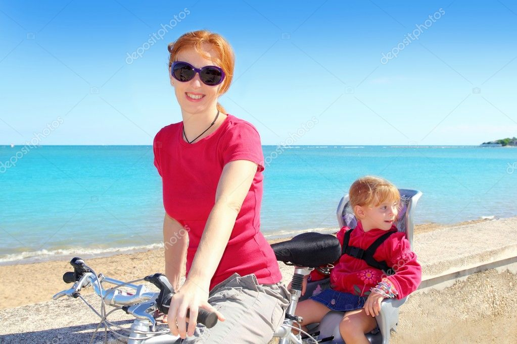 Daughter and mother on bicycle in beach sea vacation outdoor — Stock Photo #5554237