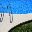Blue tiles swimming pool with green grass garden — Stock Photo